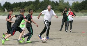 Brian Kerr plays football with touring children from the Al-Helal academy in Gaza. Photograph: Niall Carosn/PA