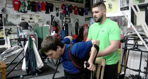 Nathan Kirwan with Colin O'Shaughnessy of the Elite Gym: Mr Kirwan, who has a spinal cord injury, wears an exoskeleton in the Cork gym. Photograph: Kathleen Harris