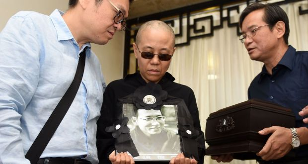 Late Nobel laureate Liu Xiaobo's wife Liu Xia holding a portrait of Liu Xiaobo and receiving the ashes  in an urn at a funeral parlour in the Chinese city of Shenyang, Liaoning province, on July 15, 2017. Photograph: Shenyang Municipal Information Office/AFP