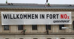 "Activists attach a banner that reads ""Welcome to Fort NOx"" to Germany's ministry of transport as ministers and car executives meet to discuss ways to cut inner-city pollution. Photograph: Reuters/Hannibal Hanschke"