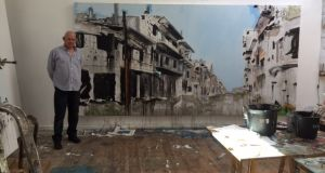 Irish painter Brian Maguire stands beside one of his paintings of devastated eastern Aleppo, after it was reconquered by Syrian government forces.
