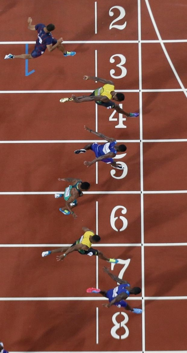Justin Gatlin (bottom) crosses the line to win the men's 100m final. Photo: Getty Images