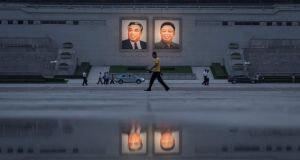 Pedestrians and vehicles pass before portraits of late North Korean leaders Kim Il-Sung (left) and Kim Jong-Il  in Pyongyang. Photograph: Ed Jones  AFP/Getty Images