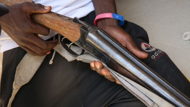 A Civilian Joint Task Force member shows off a rifle captured from Boko Haram.