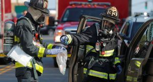 Firefighters remove items from a vehicle in which several drug overdose victims were found, in Chelsea, Massachusetts. Photograph: Brian Snyder/Reuters