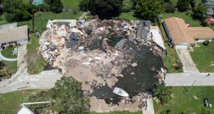 A sinkhole (above) at Land O'Lakes, Florida has expanded and now stretches 260ft (80m) at its widest point, the Tampa Bay Times reported. Photograph: Luis Santana/Tampa Bay Times/AP
