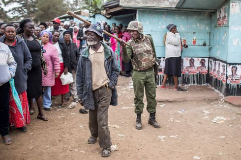 KENYAN ELECTION: A Kenya Administration police officer monitors access to a polling station at Kariokor Community Centre in Nairobi during general elections. Photograph: Luis Tato/AFP/Getty Images
