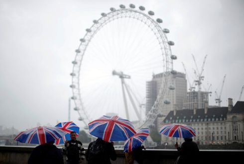 LONDON EYE: Tourists carrying Union Flag umbrellas shelter from the rain in front of the London Eye wheel in London. Photograph: Hannah McKay