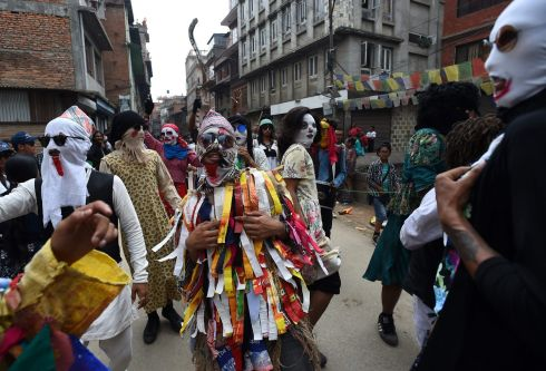 KATHMANDU FESTIVAL: Participants wear masks at the Neku Jatra-Mataya festival in Patan, on the outskirts of Kathmandu, Nepal. The Buddhist festival marks the victory of Sakyamuni Buddha over Mara, where devotees pray for the souls of departed family members. Photograph: Prakash Mathema/AFP/Getty Images
