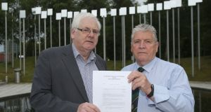 Michael Gallagher (left) who lost his son Aiden, and Stanley McComb (right), who lost his wife Ann in the Omagh bombing hold a writ in the Omagh Memorial Garden. Photograph: Niall Carson/PA