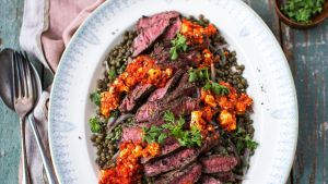 Arrange the lentil salad on  platters with steak slices, htipiti sauce and sprinkle the remaining parsley over the top