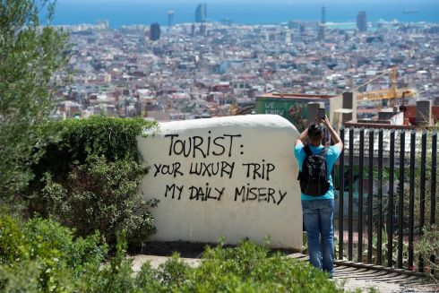 "TOURIST TRAP: A tourist takes a snap at Park Guell, Barcelona, Spain next to a wall with graffiti reading ""Tourist: your luxury trip - my daily misery"". Spanish activists have launched initiatives against what they consider to be a lack of control of mass tourism in cities such as Barcelona and Palma de Mallorca. Photograph: Josep Lago/AFP/Getty Images"