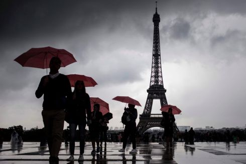 PARIS RAIN: Tourists walk with umbrellas at the Trocadero near the Eiffel Tower amid rain in Paris. Photograph: Philippe Lopez/AFP/Getty Images