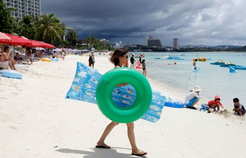 WAR OF WORDS: Tourists on Tumon beach on the island of Guam, a US Pacific territory, as a war of words between North Korea and the US over missile threats to the island continues. Photograph: Erik De Castro/Reuters