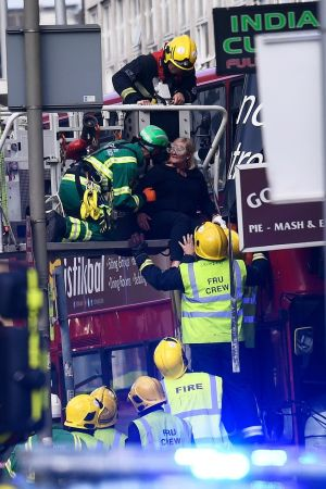 LONDON CRASH: Emergency personnel rescue a woman trapped on the top floor of a bus after it crashed into a shop on Lavender Hill in Clapham, London, Britain. Photograph: Dylan Martinez/Reuters