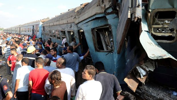 People gather at the site of a train collision in the area of Khorshid in Egypt's Mediterranean city of Alexandria