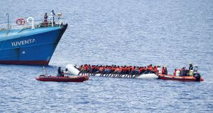 "Migrants on a dinghy are rescued by German NGO Jugend Rettet ship ""Juventa"" crew in the Mediterranean sea. Photograph: Stefano Rellandini/Reuters"