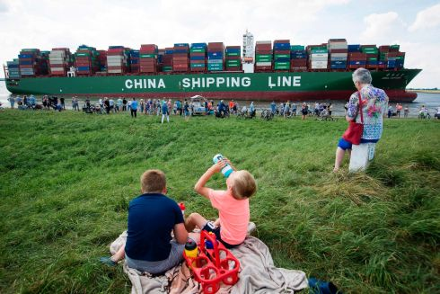 LAND HO: Onlookers gather at the site where the Hong Kong-flagged CSCL Jupiter container ship is stranded on the Westerschelde estuary near the Dutch town of Bath following a grounding incident on Monday. Photograph: Kristof  Van Accom/AFP/Getty Images