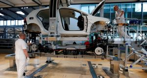 Workers assemble an e-Golf electric car at the Volkswagen plant in Dresden: The German economy growth rate for the first quarter has been revised up to 0.7 per cent on the quarter. Photograph: Fabrizio Bensch/Reuters