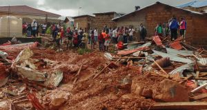 Residents of Sierra Leone's capital Freetown view damage to property on Tuesday due to a mudslide in the suburb of Regent. Photograph: Ernest Henry/EPA
