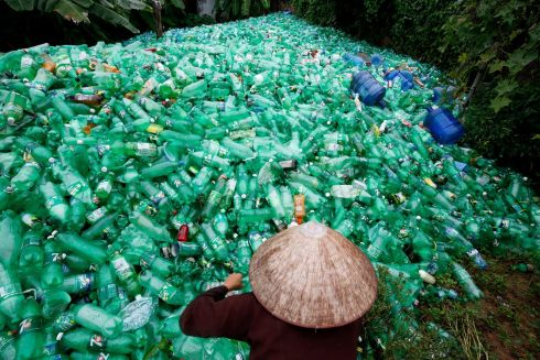 BOTTLE IT: A woman sorts out recyclable plastic soft drink bottles at Xa Cau village, outside Hanoi, Vietnam.  Photograph: Kham/Reuters