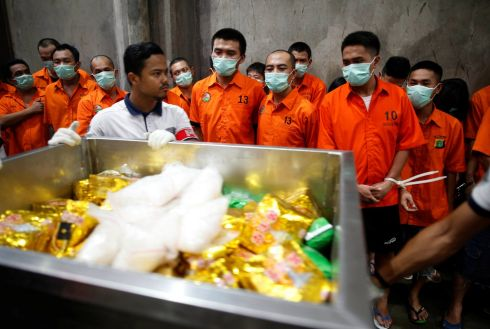 UP IN SMOKE: Drug suspects watch as recently confiscated narcotics, including 1.4 tonnes of methamphetamine and a large amount of ecstasy pills, are wheeled to an incinerator by police following a ceremony by drug enforcement agencies in Jakarta, Indonesia.  Photograph: Darren Whiteside/Reuters