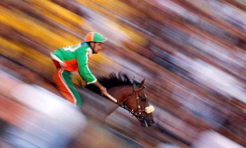 "RIDE ON: Andrea Coghe, jockey of the ""Selva"" (Forest) parish, rides during the fourth practices for the Palio of Siena, Italy.  Photograph: Stefano Rellandini/Reuters"