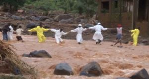 People wearing protective suits hold hands as they cross a river on Tuesday after a mudslide in the mountain town of Regent, Sierra Leone. Photograph: Reuters TV