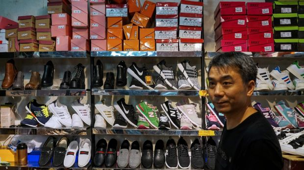 "A Chinese salesman sells copies of various American footwear brands inside a shopping complex in Shanghai. Beijing has warned it ""will not sit idle"" if a US probe into its intellectual property practices leads to sanctions. Photograph: Chandan Khanna/AFP/Getty Images"