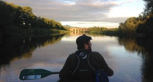 Dan  paddles down the Barrow river in an open-top Canadian canoe