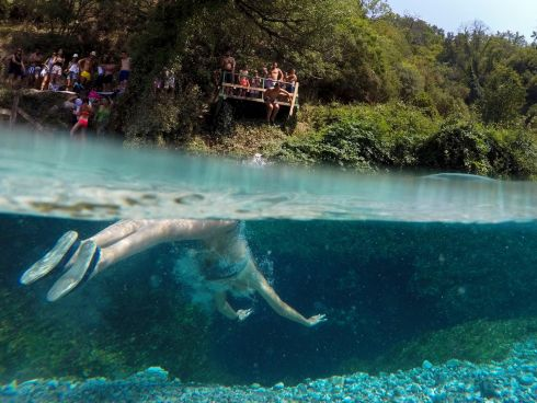 GOING SWIMMINGLY: A man tries to cool off in the Blue Eye, near the city of Sarandë, Albania. Photograph: Gent Shkullaku/AFP/Getty Images
