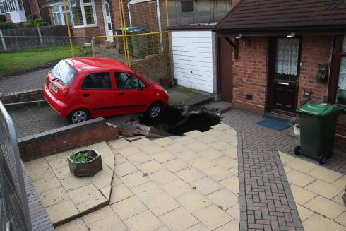 SINKING FEELING: A view of a huge sinkhole that has opened up yards from a house in Churchfields Road, Wednesbury, England. Photograph: Aaron Chown/PA Wire