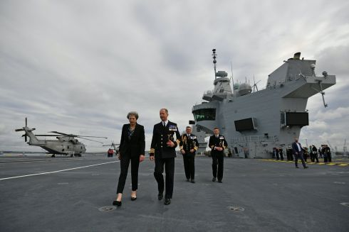 TOUCH BASE: British prime minister Theresa May talks with the captain of the British aircraft-carrier HMS Queen Elizabeth, at Portsmouth naval base, England. Photograph: Ben Stansall/Pool/Reuters