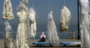 A veiled woman sits  on a bench near an installation of wedding dresses by Lebanese artist Mireille Honein and Abaad activist organisation  at Beirut's corniche in April. The installation was a criticism of Lebanon's law allowing rapists who married their victims to go free. Photograph:   Patrick Baz/AFP/Getty Images