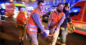 A woman is evacuated from the Bataclan theatre after the terror attack in Paris on November 13th, 2015. Photograph: Thibault Camus/AP
