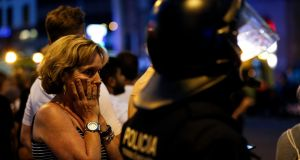 A woman gestures as she is escorted out by Spanish policemen outside a cordoned off area. Photograph: Pau Barrena/Getty Images