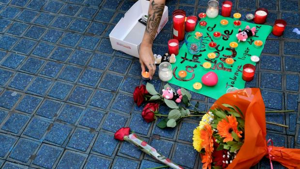 A woman places a candle next to flowers and a message to the victims on August 18th. Photograph: Javier Soriano/AFP/Getty Images