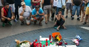 People mourn in front of candles and flowers placed on a Spanish artist Miro's mosaic on the site of a van attack in Barcelona in which 13 people died. Photograph: EPA