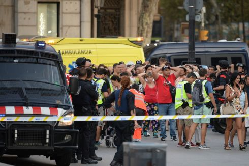 Policemen check the identity of people standing with their hands up. Photo: Josep Lago/AFP/Getty