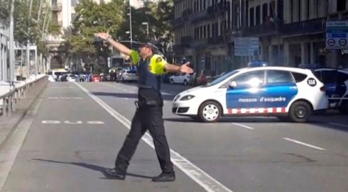 A still image from video shows a police officer gesturing while walking across a road, after a van crashed into people in the centre of Barcelona. Photo: via Reuters