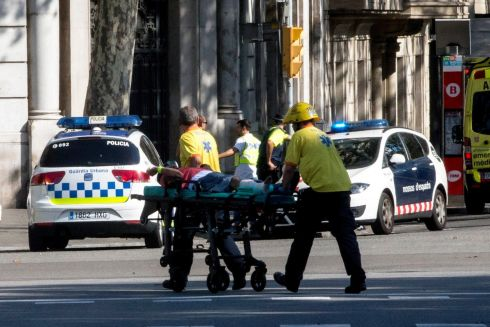 Police officers and emergency service workers move an injured man, after a van crashes into pedestrians in Las Ramblas. Photo: Quique Garcia/EPA