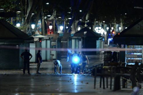 Police check the area after towing away the van. Photograph: Josep Lago /AFP/Getty Images