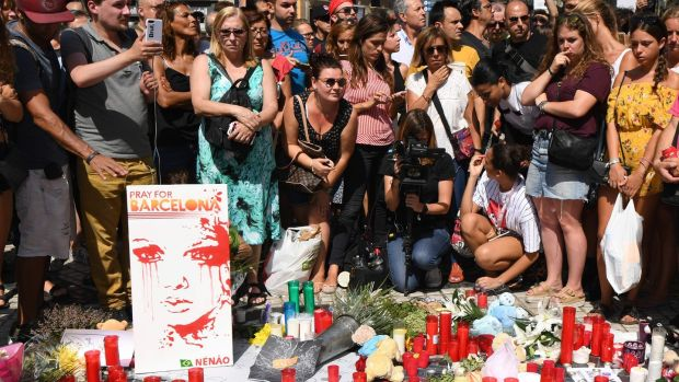 'Pray for Barcelona': Crowds have gathered on Las Ramblas to pay tribute to the victims of the attack which killed 13 and injured more than 100. Photograph: Pascal Guyot/AFP/Getty Images
