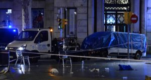 The van which was driven into a crowd, killing at least 13 people and injuring around 100 others in Barcelona,  is towed away by police  on Friday. Photograph: AFP