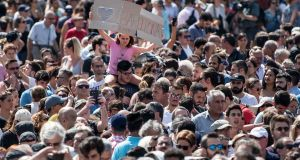 A girl holds up a banner as people gather in Placa de Catalunya to observe a one minute's silence for the victims of Thursday's terrorist attack. Photograph: Carl Court/Getty Images