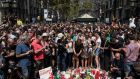 People gather around tributes laid on Las Ramblas after a one minute's silence for the victims of Thursday's terrorist attack. Photograph: Carl Court/Getty Images