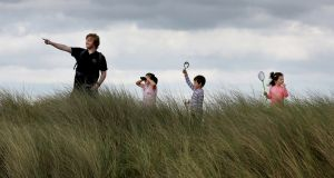Padraic Creedon of Global Action Plan with, from left, Rosanna Drewilieu (7) from Killester, Dublin, Michael O'Brien (5) from Edenderry, Co Offaly and his sister Hannah (3) on the look-out for the natural heritage of Dublin's Bull Island for National Heritage Week 2017.  Photograph: Mark Stedman