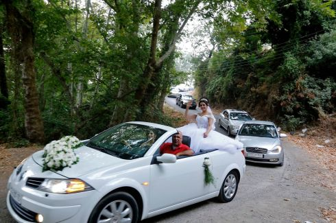 LIFE GOES ON: A Syrian bride waves from the back of a car during a wedding in Wadi al-Nasara west of Homs. Photograph: Louai Beshara/AFP/Getty Images