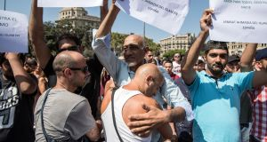 A man hugs  Muslim men as they hold posters denouncing yesterday's terrorist attack on Las Ramblas, following a one-minute silence for the victims of Thursday's attack. Photograph: by Carl Court/Getty Images