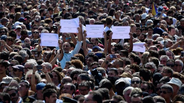 People brandish messages before a minute's silence for the victims of the Barcelona attack at Plaça de Catalunya on Friday. Photograph: Javier Soriano/AFP/Getty Images